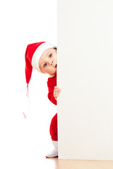 small Santa claus child looking from behind the placard or banne
