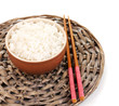 Bowl of rice and chopsticks on wicker mat isoalted on white