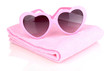 Pink heart-shaped sunglasses on towel isolated on white