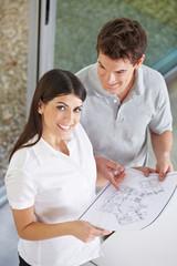 Paar hält Bauplan in der Hand