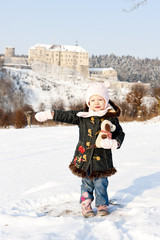 standing little girl and Cesky Sternberk Castle in winter at bac