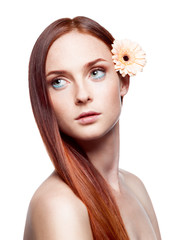 portrait of young red-haired female with flower in hair