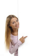 Hübsche Frau zeigt seitlich leeres Plakat