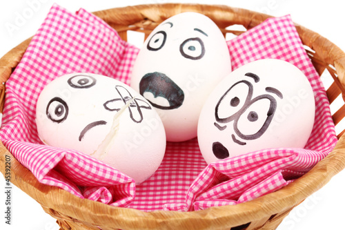 White eggs with funny faces in basket isolated on white