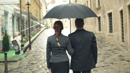 Business people walking with umbrella in the city