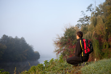 Tourist sitting by the river in the early misty morning