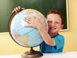 Niño en una escuela abrazando el mundo,planeta tierra.