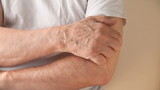 a man scratches a persistent itch on his arm