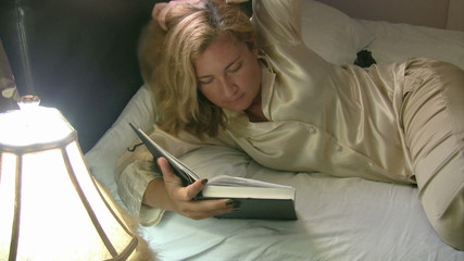 Woman reading and trying to sleep