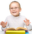 Cute cheerful little girl reading book