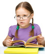 Cute little girl reading book wearing glasses