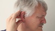 senior man suffering from pain in and around his ear