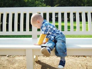 Little boy on a big bench in park