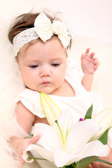 Adorable baby girl in white dress lying with flower