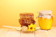 Jar of honey and honeycomb on wooden table on orange background