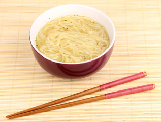 asian noodles in bowl on bamboo mat