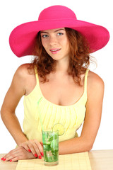 Smiling beautiful girl sitting at the table with beach hat and