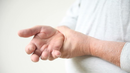 a man checks the area around his sore thumb