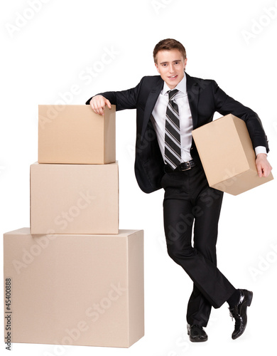 Manager in suit stands near pile of cardboard boxes
