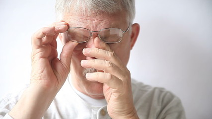 older man rubs the area affected by his glasses