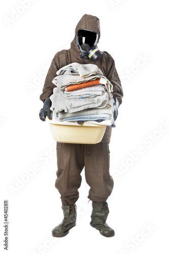 Man in Hazard Suit holding dirty towels and looking at the camer
