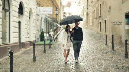 Young couple walking with umbrella in the city, steadycam shot