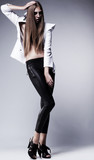 Young woman in black leggings posing. Glamour, beauty style