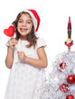 Happy Little Girl Wearing Santa Hat with heart form lollipop by