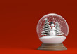 snowglobe with snowman and trees on a red background copy space