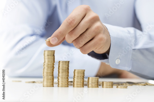 Savings, male hand stacking gold coins