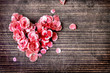 Heart with petal from flowers on wooden table