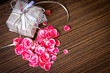 Gift bow with heart from petal of flowers on wooden table