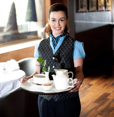 Pretty waitress posing with tea for guests