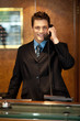 Cheerful front desk executive attending phone call