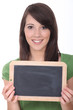 woman holding a blackboard left blank for a message