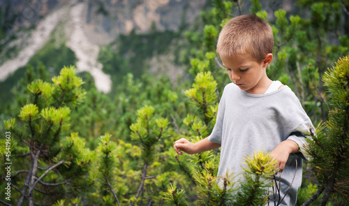 Portrait of four year old boy walking outdoors in the mountains.