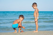 Two brothers playing on the beach.