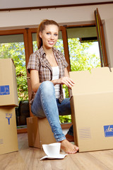 A beautiful single young woman unpacking boxes and moving into a