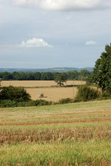 View of English fields with a tractor ploughing in the distance