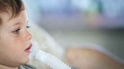 Sick little boy  using nebulizer to inhale medicine