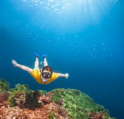 Young explorer snorkeling underwater
