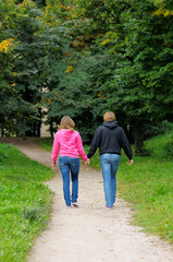 Young couple walking in autumnal park together