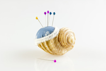 pincushion in shell with pins isolated horizontal