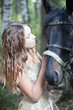 Attractive blond girl with her horse.
