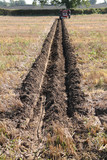 A Tractor at the Far End of a Ploughed Furrow in a Field. poster