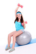 Woman working out with dumbbells on fitness ball