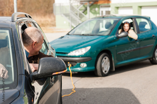 Man helping woman by pulling her car
