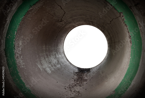 Glowing end of an empty round concrete tunnel interior