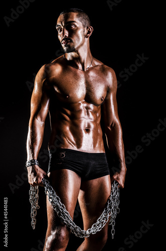 Bodybuilder with chains in dark
