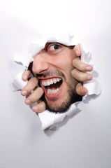 Male face through the hole in paper